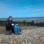 Nicole sitting by the beach with a cup of tea and a book taking advantage of free time to dedicate to her doctoral studies.