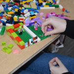 Image of a person building a model using LEGO bricks